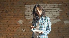 Το κορίτσι λευκαίνει το τουβλότοιχο Το κορίτσι Hipster ασπρίζει τους τοίχους στο σπίτι Κρατά στα χέρια μιας βούρτσας με το χρώμα φιλμ μικρού μήκους