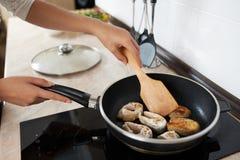 Το κορίτσι μαγειρεύει τα ψάρια τηγανητών Στοκ Εικόνα