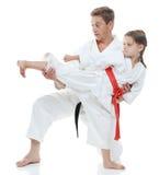 Το κορίτσι μαθαίνει να κτυπά το πόδι λακτίσματος στο άσπρο υπόβαθρο Στοκ Φωτογραφία