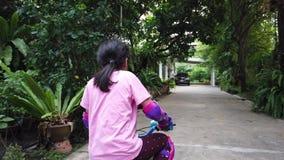 Το κορίτσι μαθαίνει να οδηγά ένα ποδήλατο με την πλήρη προστασία απόθεμα βίντεο