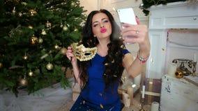 Το κορίτσι μεταμφιέσεων κάνει selfie σε μια γιορτή Χριστουγέννων κοντά στο χριστουγεννιάτικο δέντρο, νέος εορτασμός έτους στη μάσ απόθεμα βίντεο