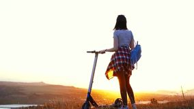 Το κορίτσι με ένα ηλεκτρικό μηχανικό δίκυκλο στέκεται με την πίσω και εξετάζει το ηλιοβασίλεμα, αργό MO