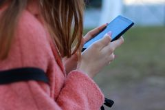 Το κορίτσι με ένα κινητό τηλέφωνο στο χέρι της είναι στην οδό στοκ εικόνα