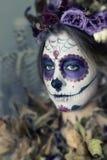 Το κορίτσι με ένα κρανίο μεξικανός ζάχαρης αποτελεί Στοκ Εικόνες