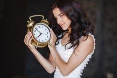 Το κορίτσι με ένα μεγάλο ρολόι σε ένα σκοτεινό υπόβαθρο Στοκ Εικόνα