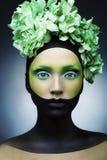 Το κορίτσι με δημιουργικός πράσινος και ο Μαύρος και πράσινος αποτελούν και λουλούδια στοκ εικόνα