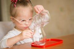 Το κορίτσι με το κάτω σύνδρομο χύνει ήπια το νερό από μια κανάτα σε μια κανάτα στοκ εικόνα