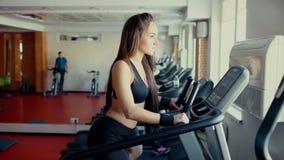 Το κορίτσι με το μακρυμάλλες περπάτημα, που τρέχει treadmill στη γυμναστική workout 4 Κ απόθεμα βίντεο