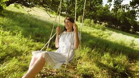 Το κορίτσι με μακρυμάλλη στο άσπρο φόρεμα γελά κυλώντας στην ταλάντευση κάτω από το θερινό δρύινο δέντρο σε ένα πάρκο το φθινόπωρ φιλμ μικρού μήκους
