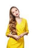 Το κορίτσι με μακρυμάλλη στο κίτρινο φόρεμα, αυτό είναι απομονωμένο σε ένα άσπρο β Στοκ Φωτογραφίες
