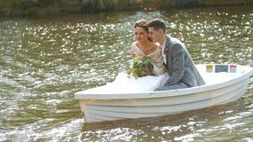 Το κορίτσι με μια ανθοδέσμη και ο σύζυγός της κολυμπούν σε μια λίμνη Το Newlyweds είναι ευτυχές φιλμ μικρού μήκους