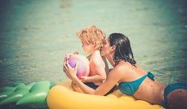 Το κορίτσι με το παιδί μικρών παιδιών κολυμπά στο κίτρινο στρώμα αέρα στο νερό το καλοκαίρι στοκ φωτογραφία