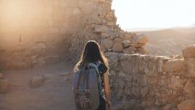 Το κορίτσι με το σακίδιο πλάτης ερευνά τις αρχαίες καταστροφές ερήμων Όμορφοι περίπατοι γυναικών μεταξύ των τοίχων φρουρίων βουνώ απόθεμα βίντεο
