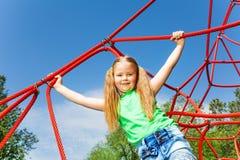 Το κορίτσι με τα ευθέα χέρια κρατά το κόκκινο σχοινί καθαρού Στοκ Εικόνες