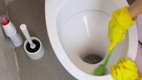 Το κορίτσι με τα κίτρινα λαστιχένια γάντια καθαρίζει την τουαλέτα με μια βούρτσα Βλέποντας άνωθεν απόθεμα βίντεο