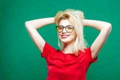 Το κορίτσι με τα μακριά ξανθά μαλλιά, Eyeglasses και το γοητευτικό χαμόγελο που φορά την κόκκινη κορυφή θέτει στο πράσινο υπόβαθρ Στοκ εικόνες με δικαίωμα ελεύθερης χρήσης