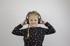 Το κορίτσι με τα μεγάλα μαύρα ακουστικά εξετάζει τη κάμερα στοκ εικόνες με δικαίωμα ελεύθερης χρήσης