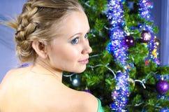 Το κορίτσι με τα μπλε μάτια γύρω από το χριστουγεννιάτικο δέντρο Στοκ εικόνες με δικαίωμα ελεύθερης χρήσης