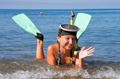 Το κορίτσι με τα πτερύγια και τη μάσκα βρίσκεται στη θάλασσα στοκ εικόνα