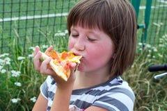 Το κορίτσι με την ευχαρίστηση τρώει μια πίτσα στοκ εικόνα με δικαίωμα ελεύθερης χρήσης