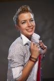 Το κορίτσι με την κοντή τρίχα στο μπεζ πουκάμισο στο γκρίζο υπόβαθρο Στοκ εικόνες με δικαίωμα ελεύθερης χρήσης