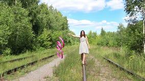 Το κορίτσι με την κορδέλλα πηγαίνει στην παλαιά ράγα στη θερινή ημέρα φιλμ μικρού μήκους