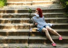 Το κορίτσι με την κόκκινη συνεδρίαση τρίχας στα σκαλοπάτια Εξαπατήστε το φύλλο Φύλλο παχνιών τσαλακωμένο έγγραφο στοκ εικόνες με δικαίωμα ελεύθερης χρήσης