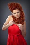 Το κορίτσι με την κόκκινη τρίχα σε μια κόκκινη κινηματογράφηση σε πρώτο πλάνο φορεμάτων Στοκ Εικόνα
