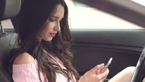 Το κορίτσι με την πιστωτική κάρτα και το τηλέφωνο κάθεται στο αυτοκίνητο απόθεμα βίντεο
