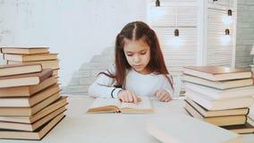 Το κορίτσι με την όμορφη μαύρη τρίχα κάθεται σε έναν πίνακα και διαβάζει τη λογοτεχνία απόθεμα βίντεο
