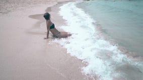 Το κορίτσι με τη δέσμη τρίχας βρίσκεται στην υγρή παραλία άμμου απολαμβάνει τα κύματα απόθεμα βίντεο
