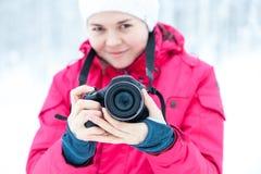 Το κορίτσι με τη κάμερα στο υπόβαθρο του χειμερινού χιονιού Στοκ Εικόνες
