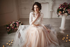 Το κορίτσι με τη σύνθεση σε ένα γαμήλιο φόρεμα κάθεται σε ένα όμορφο δωμάτιο Στοκ Εικόνες
