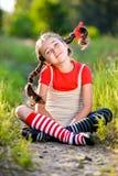 Το κορίτσι με τις πλεξίδες φαντάζεται το καλοκαίρι στη φύση στοκ εικόνες