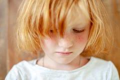 Το κορίτσι με τις φακίδες και φωτεινός κοκκινίζει στοκ φωτογραφία