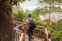 Το κορίτσι με τον μπαμπά συνεχίζεται σε μια ξύλινη σκάλα στα τροπικά βουνά στοκ εικόνες