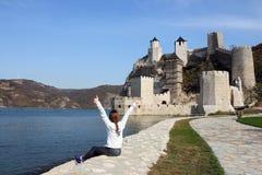 Το κορίτσι με τους αντίχειρες εξετάζει επάνω το φρούριο Golubac στοκ εικόνες