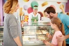 Το κορίτσι με τους γονείς επιλέγει τις γεύσεις του παγωτού στοκ φωτογραφίες