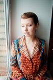 Το κορίτσι με το αναδρομικό hairstyle στο εθνικό φόρεμα κάθεται από το παράθυρο Στοκ εικόνα με δικαίωμα ελεύθερης χρήσης