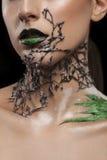 Το κορίτσι με το μαύρο λαιμό πλέγματος μόδας arround και πράσινος αποτελεί Στοκ Φωτογραφία