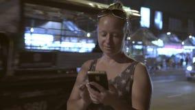 Το κορίτσι με το τηλέφωνο τη νύχτα στην οδό σε Pattaya απόθεμα βίντεο