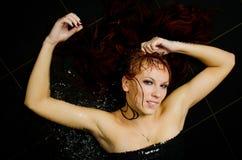 Το κορίτσι με το υγρό κόκκινο τρίχωμα Στοκ Εικόνες