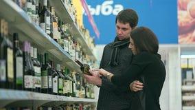Το κορίτσι με το φίλο της που επιλέγει το κρασί για το bbq κόμμα φιλμ μικρού μήκους