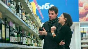 Το κορίτσι με το φίλο της που επιλέγει το μπουκάλι του κρασιού στην υπεραγορά φιλμ μικρού μήκους