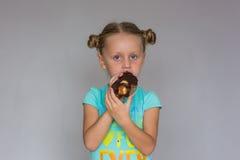 Το κορίτσι με δύο κοτσίδες που δαγκώνουν ένα κέικ σοκολάτας Στοκ Εικόνες