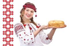 Το κορίτσι με crepes σε ένα εθνικό σχέδιο Στοκ Φωτογραφίες