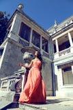 Το κορίτσι μιγάδων φορά το κομψό φόρεμα κοραλλιών με το κόσμημα, που θέτει εκτός από το antic παλάτι Στοκ Εικόνες