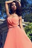 Το κορίτσι μιγάδων φορά το κομψό φόρεμα κοραλλιών με το κόσμημα, που θέτει εκτός από το antic παλάτι Στοκ Εικόνα