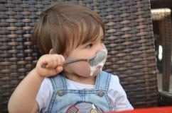 Το κορίτσι μικρών παιδιών τρώει στον υπαίθριο καφέ στοκ εικόνα