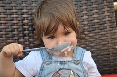 Το κορίτσι μικρών παιδιών τρώει στον υπαίθριο καφέ στοκ φωτογραφία με δικαίωμα ελεύθερης χρήσης